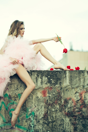 Glamour young woman with pretty face in pink dress on stony parapet with red tulips outdoor Stock Photo