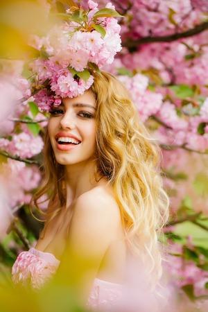 Mooie jonge vrouw in roze jurk glamour met lang krullend haar en lachend gezicht in het voorjaar bloemen bloeien