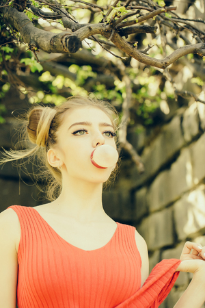goma de mascar: young pretty woman with chewing gum  in the garden with fresh spring leaves on trees on blurred natural background Foto de archivo
