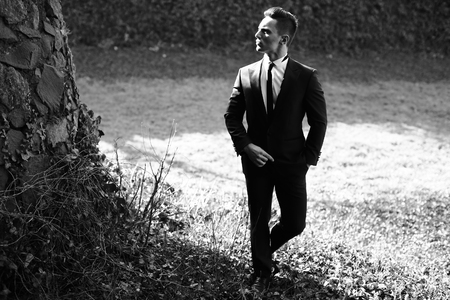 trouser legs: Man half face young handsome elegant model in suit with skinny necktie poses with hand in trouser pocket one leg backward black and white on landscape on grey background Stock Photo