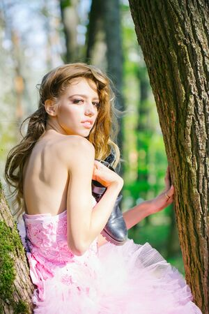 sexi: Beautiful young woman in pink glamour dress with long curly hair sitting on tree in forest Stock Photo