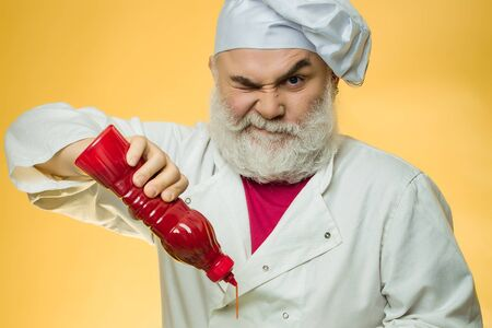 ketchup bottle: Bearded chef with ketchup bottle and grimace face in white uniform and hat on yellow background