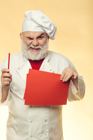 grimace: Bearded senior cook man with grimace face pointing recipe at the cookbook at the kitchen in hat on yellow background Stock Photo