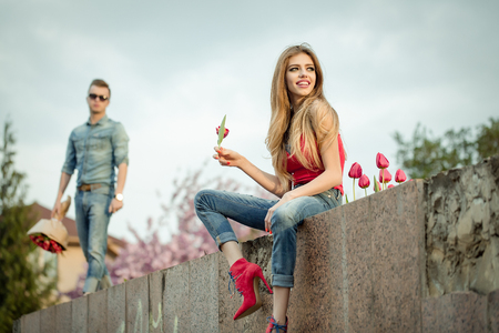 acquaintance: Young woman sits on a bench and wait at the man standing next to her, man which gives her a bouquet of rose