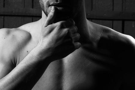 nackte brust: Junger Mann mit dem muskulösen nackten Brust und sexy Körper auf hölzernen Hintergrund im Studio, Schwarz-Weiß