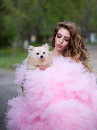 outdoor glamour: Young woman with beautiful face and long curly hair in glamour pink dress holding cute small dog outdoor
