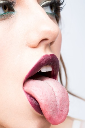 Female open mouth with lips purple lipstick and tongue Stock Photo