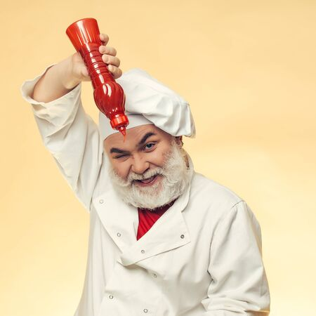 ketchup bottle: Bearded chef with ketchup bottle and smiling face in white uniform and hat on yellow background Stock Photo