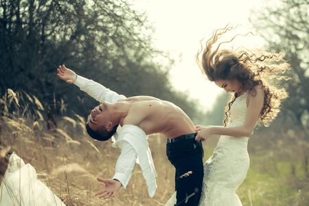 girl undressing: Young happy wedding couple of pretty woman and man undressing in field outdoor