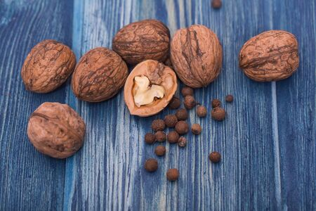 nutshells: Walnuts and small spices on blue wooden table
