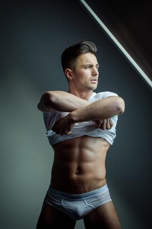 Sexy junger Mann mit muskulösen Körper in nassen T-Shirt posiert in Badehose in der Nähe von Fenster mit nacktem Oberkörper Standard-Bild - 56714760