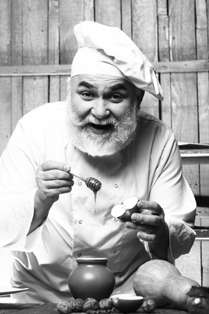 man nuts: Bearded man cook in chef hat with apple nuts pumpkin and honey on wooden background, black and white