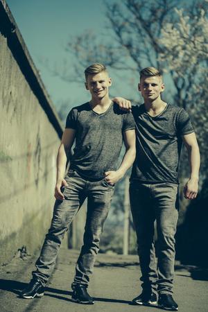 Deux frères jumeaux jeunes beaux hommes amicaux blonds en jeans câlin et sourire en plein air sur fond de streetscape Banque d'images