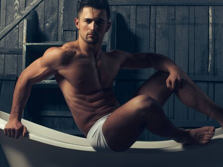 white panties: Handsome young man in white panties with bare muscular torso sitting on bathtub