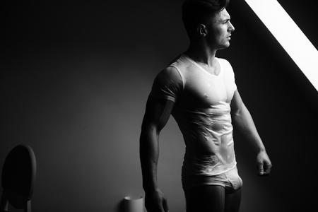 Sexy junger Mann mit muskulösen Körper in nassen T-Shirt posiert in Badehose in der Nähe von Fenster, schwarz und weiß Standard-Bild - 56716837
