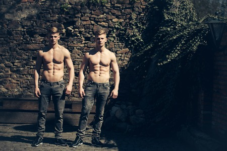 barechested: Twin young sexy strong men models brothers bare-chested in jeans stand outdoor on mural background