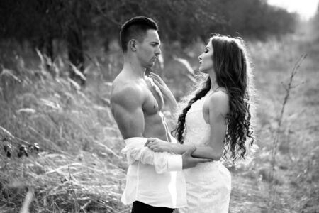 woman undressing: Young happy wedding couple of pretty woman and man undressing in field outdoor, black and white