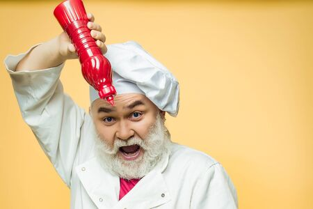 ketchup bottle: Bearded chef with ketchup bottle and emotional face in white uniform and hat on yellow background