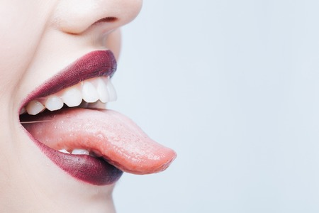 Female open smiling mouth with sexy lips purple lipstick and tongue, copy space