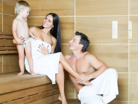 Happy family couple of young smiling woman and muscular man with son sitting in bath sauna in white towels Stock Photo