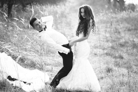 girl undressing: Young happy wedding couple of pretty woman and man undressing in field outdoor, black and white