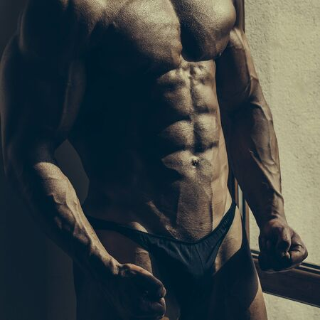 six pack: Handsome man power athletic young sexy strong bodybuilder with six pack muscles abs chest and legs on dark background