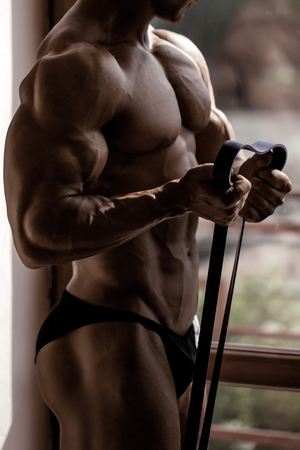 six pack: Athlete muscular bodybuilder with torso side chest six pack abdominal muscles biceps triceps train with resistance band in gym on light background