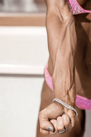 visible: Strong female arm with visible veins shows fist against blurred bodybuilder body in pink fitness bikini Stock Photo