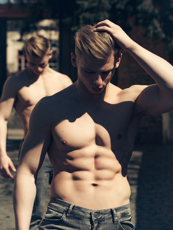 barechested: Young man sexy muscular bodybuilder macho with bare torso stylish haircut while twin brother poses outdoor on blurred background
