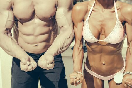 six pack abs: Fit woman and man show perfect body six pack abs muscles biceps on light background Stock Photo