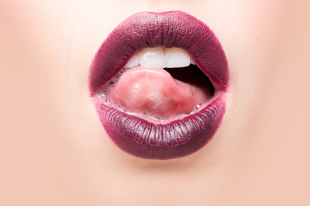beige lips: Female open mouth with sexy lips purple lipstick and tongue on beige background