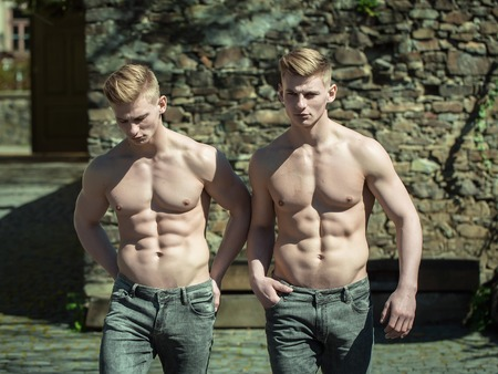 barechested: Twin muscular bare-chested young men brothers models walk shirtless in jeans on courtyard background