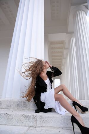 Young woman with beautiful long hair in white dress and black jacket windy day near building column Stock Photo