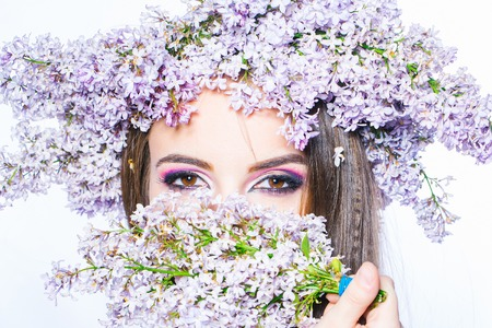 smells: Gorgeous female brunette young woman with lilac wreath on head smells spring flowers on white background