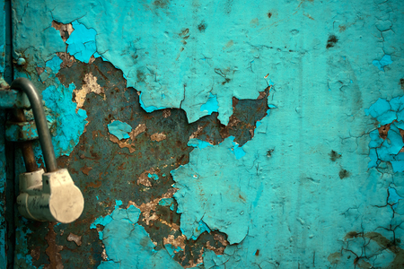 crackles: Multicolored background: rusty metal surface with blue paint flaking and cracking texture with lock