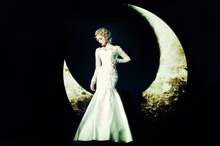crescent: Beautiful young woman with blonde hair and red lips posing on crescent moon in long evening elegant dress white color on black background Stock Photo