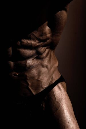 six pack: Man power athletic with great physique strong bodybuilder with six pack muscles abs chest black and white on dark background Stock Photo