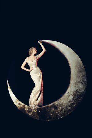 noche y luna: Hermosa mujer joven con el pelo rubio y los labios rojo que presenta en la luna creciente en el elegante vestido de noche largo de color blanco sobre fondo negro