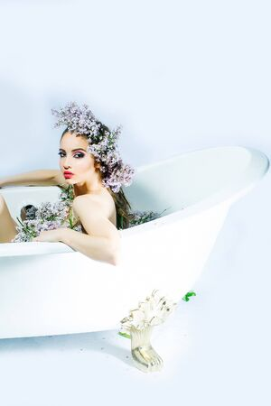 enjoys: Attractive girl with dark hair and evening makeup enjoys bath with lilac petals on white background Stock Photo