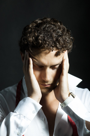 untied: Handsome man with curly hair and unshaven face in white shirt and red untied bow holding hands near head in headache on black background