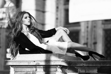 Young woman with pretty face and legs with long hair lying on stony parapeth in dress with jacket and high heels sunny windy weather, black and white