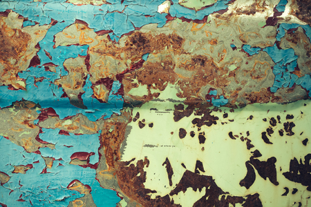 crevice: Multicolored background: rusty metal surface with paint flaking and cracking texture