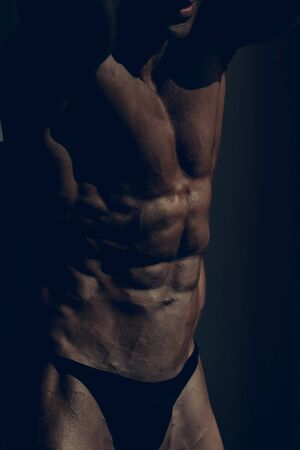 six pack: Handsome man power athletic young strong bodybuilder with six pack muscles abs and chest on dark background