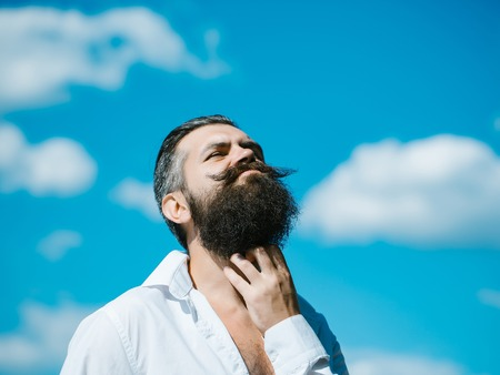 white beard: Handsome young stylish hipster man with long beard in white shirt standing outdoor on blue sky background sunny day outdoor