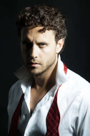 untied: Handsome man with curly hair and unshaven face in white shirt and red untied bow on black background