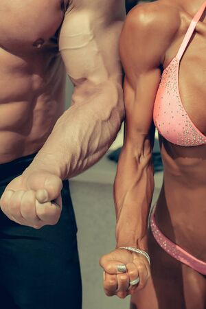 physique: Sporty couple man and woman bodybuilders show strong arms with visible veins fists muscular physique in gym on blurred background