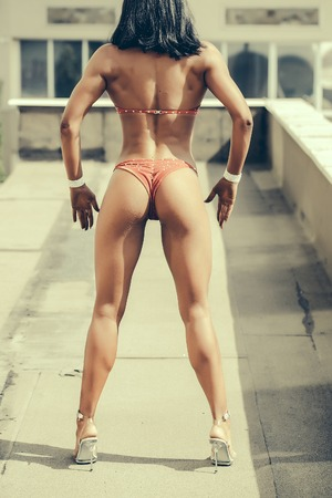 female legs: Female bodybuilder strong woman in fitness bikini stands in high heels and shows beautiful muscular body legs rear view on urban background
