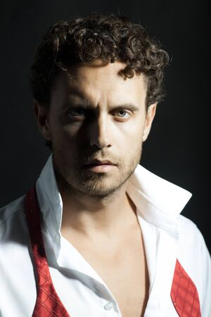 untied: Handsome sexy man with curly hair and unshaven face in white shirt and red untied bow on black background