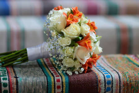 coverlet: Beautiful wedding bright bridal bouquet with white and orange flowers female floral accessory for marriage laying on colorful coverlet
