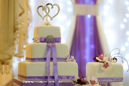 two hearts: Beautiful tasty wedding multilayer cake sweet traditional marriage dessert decorated by flowers lilac ribbons and two hearts on top on blur violet and white background